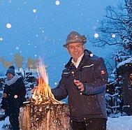 Strobl Advent, Mann wärmt sich am Feuer, © WTG