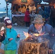 Strobl Advent, Mutter und Kind sehen beim Feuer machen zu, © WTG, Stadler